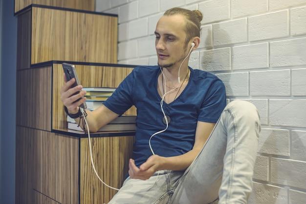 家庭環境でオーディオブックを聴くヘッドフォンで若い男。技術と近代教育の概念