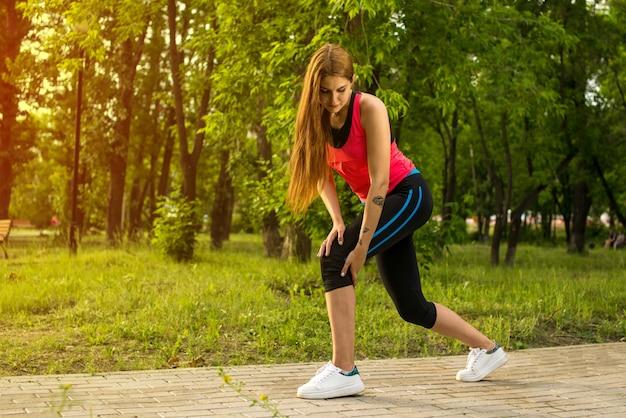 公園で走っている間痛みの女性