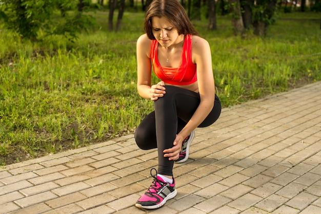 Женщина в боли во время бега в парке