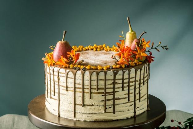 チョコレートを注ぎ、梨と海クロウメモドキで飾られた蜂蜜ケーキ