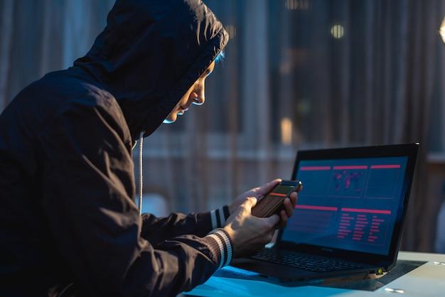 Мужской хакер в капюшоне держит телефон в руках, пытаясь украсть доступ к базам данных. концепция кибербезопасности
