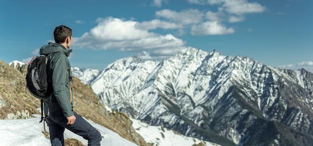 Человек празднуют успех стоя на снежных горах. понятие мотивации и достижения своих целей