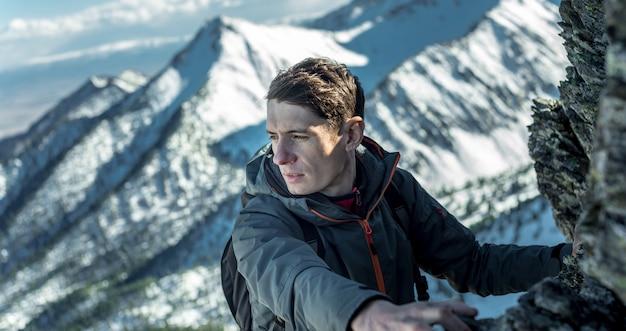 トップの雪に覆われた山々に岩の上をクロール男観光客。動機と目標の達成