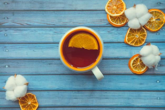 コットンボールと青い木製のテーブルの上のオレンジと温かいお茶のカップ