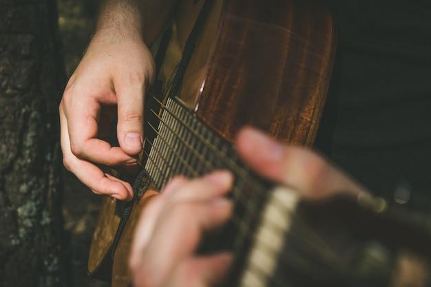 ギターの指板に弦を形成する指。ギターで遊ぶ男性の手。