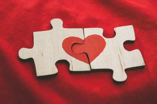 Красное сердце нарисовано на кусочки деревянной головоломки, лежащие рядом друг с другом на красном фоне.