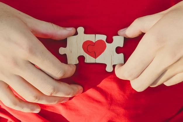 赤いハートは、赤の背景に男性の手でパズルのピースに描かれています。愛 。聖バレンタインの日