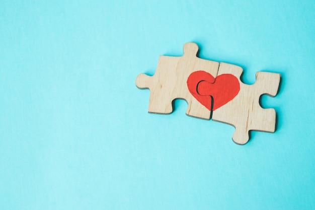 Красное сердце нарисовано на кусочки деревянной головоломки, лежащие рядом друг с другом на синем фоне. любить . день святого валентина