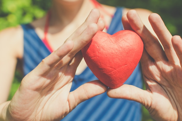 赤いハートを保持している関係と愛の女性の手