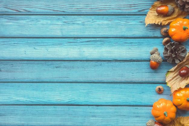 秋の紅葉、装飾的なカボチャ、ドングリ、青い木製の背景上のコーン