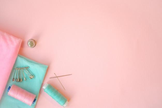 ミシンアクセサリー、ピンクの背景にターコイズブルーとピンクの生地。生地、ピン、糸、針。