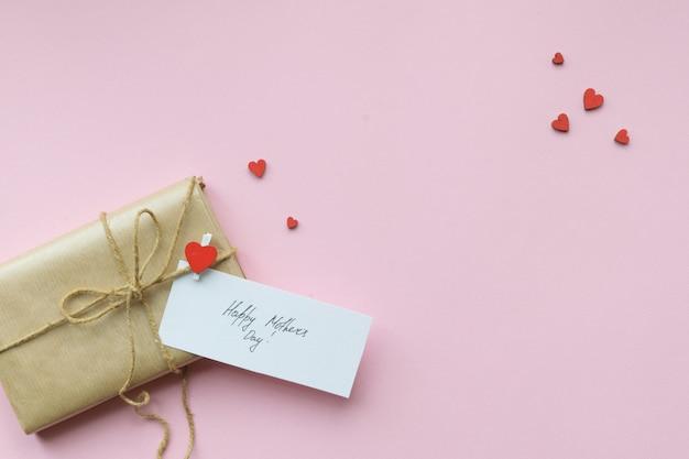 Подарок, завернутый в коричневую крафт-бумагу и галстук-пеньку. подарочная коробка с поздравлением на день матери. вид сверху.