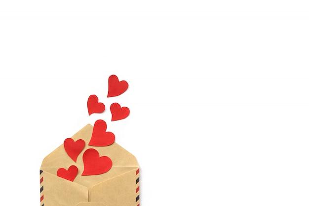 バレンタインの日、白い背景で隔離クラフトエンベロープから赤いハート。コンセプトが大好きです。コピースペース