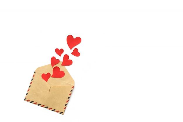 バレンタインデー、白い背景で隔離の封筒から赤いハート。コンセプトが大好きです。コピースペース