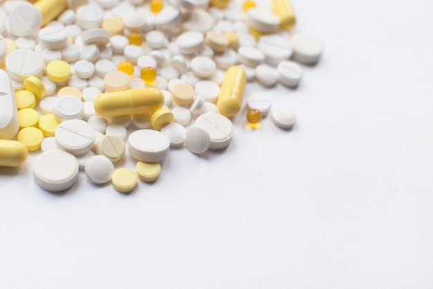 黄色と白の錠剤と白い背景で隔離の丸薬の束をクローズアップ。医療薬局のコンセプト。セレクティブフォーカス。