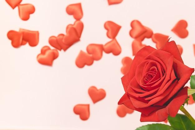 バレンタインデーの背景、ピンクの背景に赤いハートと赤いバラ、カードおよび結婚式の背景
