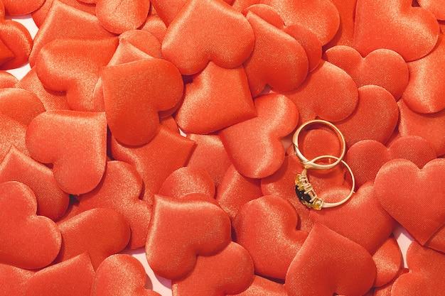 Два золотых обручальных кольца на фоне красных атласных сердец