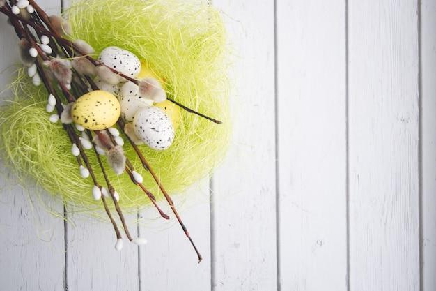 Пасхальные украшения. веточки вербы и декоративные яйца в гнездах на деревянном фоне