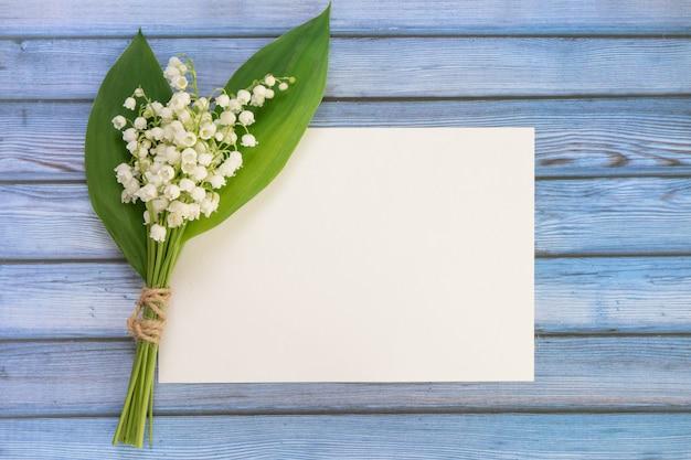 Букет цветов рядом с пустым листом бумаги