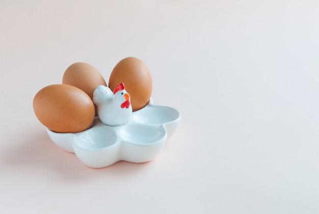 ピンクの背景の卵と白いセラミックエッグホルダー。セラミックチキン