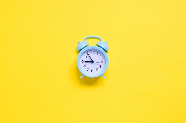 Синий будильник на желтом фоне
