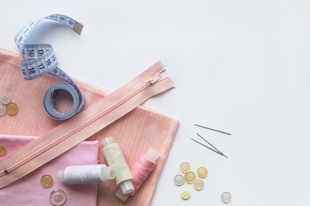 ピンクの布地、ミシン糸、ジッパー、針、ボタン、ミシンセンチ。平面図、フラットレイ
