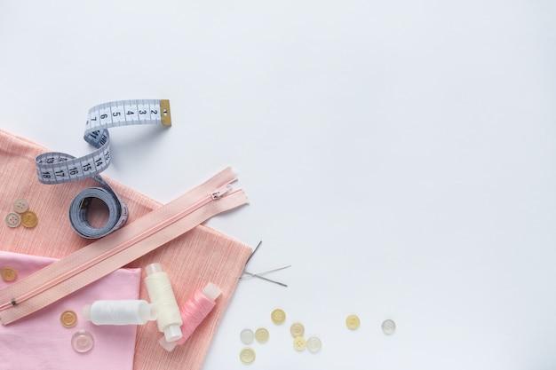 生地、ミシン糸、針、ボタン、ミシンセンチ。平面図、フラットレイ