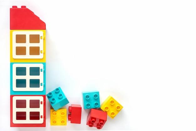 白い背景の上の大小のプラスチック製のコンストラクターのレンガの家。人気のおもちゃ
