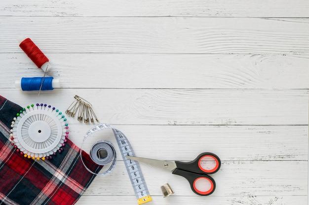 ミシンアクセサリー。白い木製の背景に格子縞の布。
