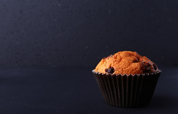 暗い背景においしいチョコレートカップケーキ