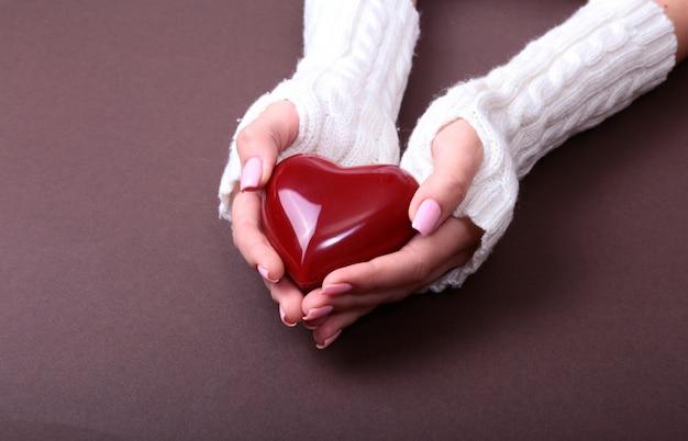 女性は彼女の手に赤いハートを保持します