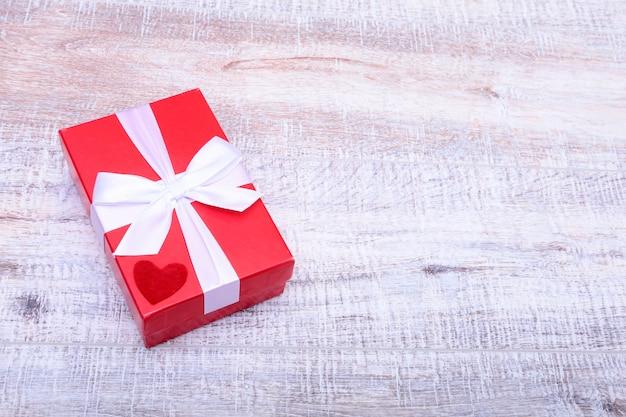 Красная подарочная коробка с бантом из ленты открыта на старинном белом деревянном столе