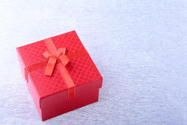 木材の背景に弓でギフトボックス。クリスマスの飾り
