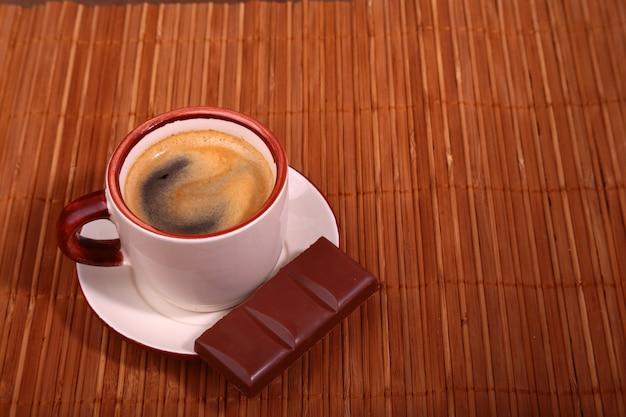 コーヒーカップと木製のテーブルテクスチャにチョコレート。コーヒーブレイク