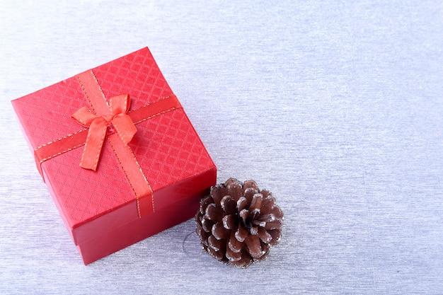 ウッドの背景に弓とクリスマスボールのギフトボックス