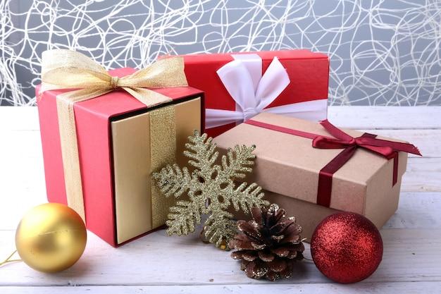 木製の背景に弓とクリスマスボールのギフトボックス