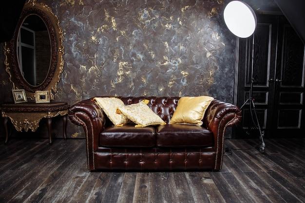 部屋の灰色のコンクリートテクスチャ壁とダークブラウンヴィンテージ美しい豪華なソファのインテリア。