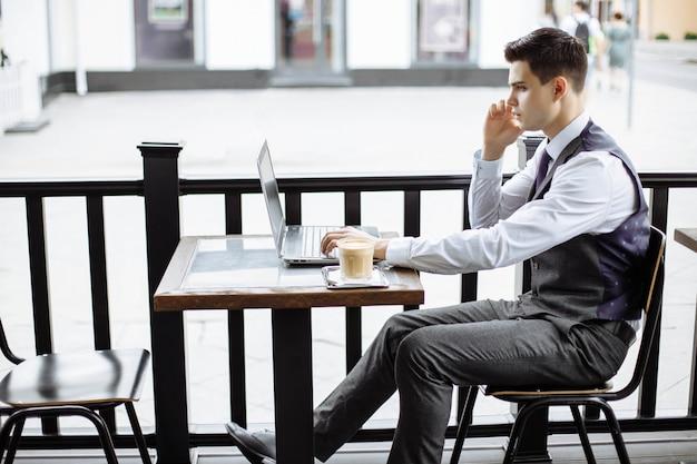 Молодой успешный деловой человек сидит в открытом городском кафе с ноутбуком и разговаривает по телефону
