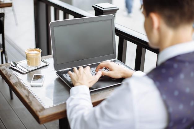 コーヒーショップでノートパソコンを使用してのビジネスマン。