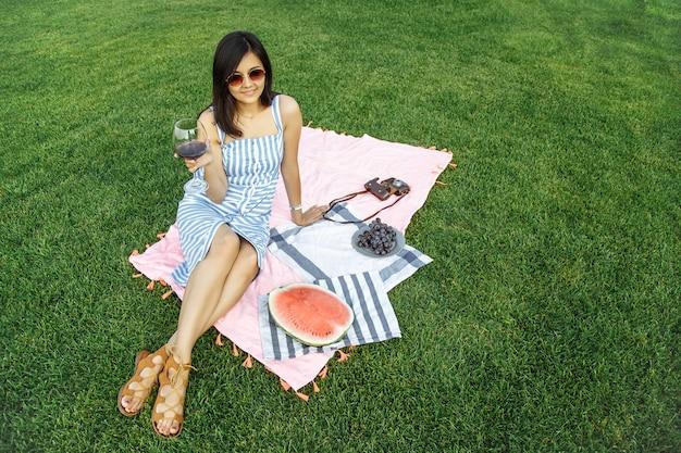 美しい少女は、ピクニックにワインを楽しんでいます。