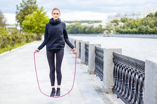 スポーティな女性が屋外で縄跳びでウォーミングアップします。