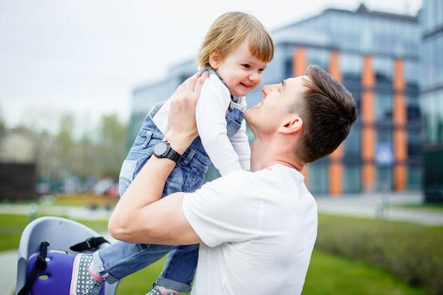 自転車に乗る前に、若い父親が小さな娘を椅子に座らせます。