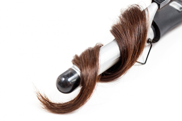 白い背景で隔離のカーリングアイロンと巻き毛の暗い髪
