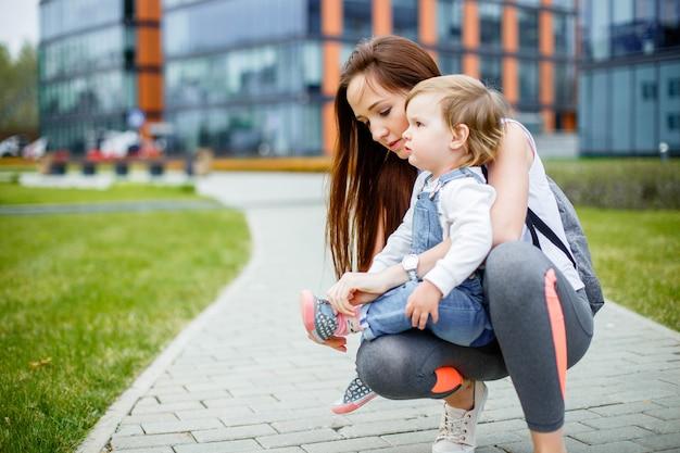 散歩に彼女の娘を持つ若い母親