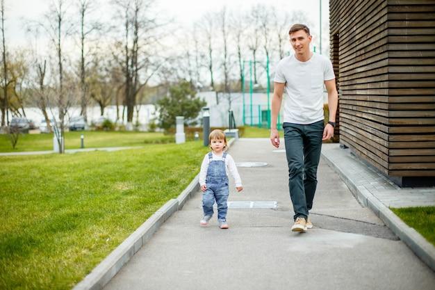 都市公園を歩いて彼の娘と若い父親