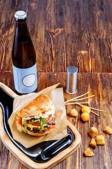 Вкусный гамбургер, закуски и пиво на деревянном столе