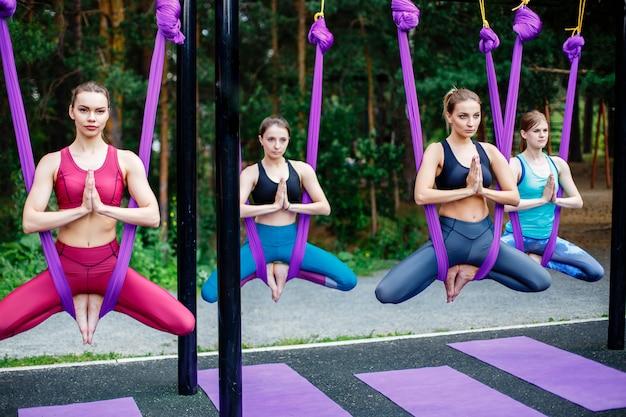 屋外の紫色のハンモックで空中ヨガの練習をしている若い女性のグループ
