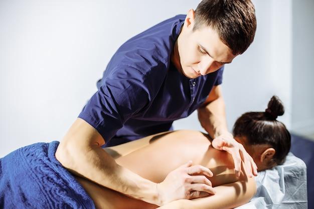Молодой массажист делает массаж спины женщине
