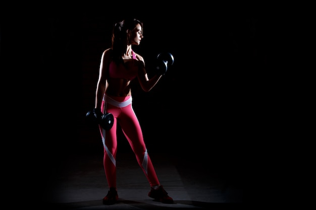 若い美しいフィットネス女性がジムでトレーニングします。