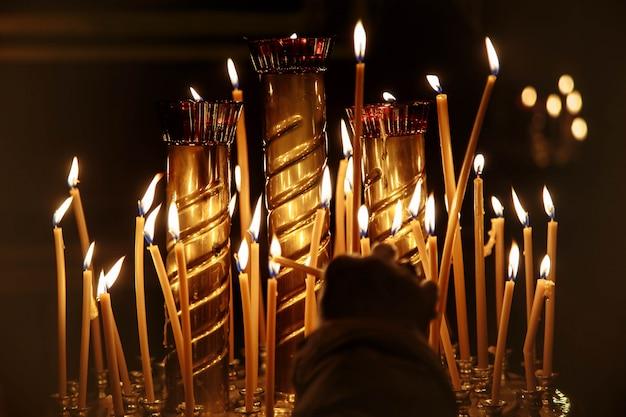 女性の手は暗い教会でろうそくを点灯します。